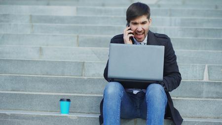 스트레스가 전화 및 거리에 계단에 앉아 랩톱 컴퓨터를 가지고 젊은 비즈니스 사람. 직장 개념에서 거래 문제가 사업가