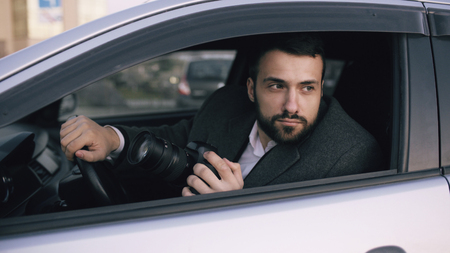 Young private detective man sitting inside car and photographing with dslr camera Stock Photo