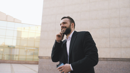 Young bearded business man talking on cell phone making deals with cup of coffee near modern office buildings