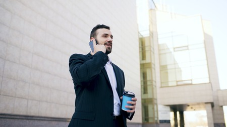 young bearded business man talking at smartphone with cup of coffee near office buildings outdoors