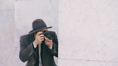 Closeup of young paparazzi man in hat photographing celebrities on camera while spy behind the wall Stock Photo