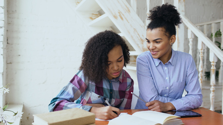 Teenage curly haired mixed race young girl sitting at the table concentrating focused learning lessons and her elder sister helps her studying