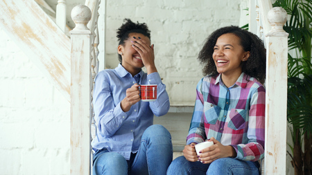 Two african american curly girls sistres sitting on stairs have fun laughing and chatting together at home