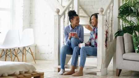 Twee Afrikaanse-Amerikaanse krullende meisjes sistres die op de trap zitten, hebben plezier aan het lachen en samen te chatten thuis Stockfoto