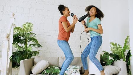 Gemengde ras jonge grappige meisjes dans zingen met föhn en kam springen op de sofa. Zusters plezier vrije tijd in woonkamer thuis concept