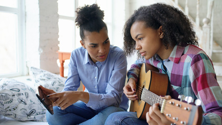Mixed race young woman with tablet computer sitting on bed teaching her teenage sister to play acoustic guitar at home Reklamní fotografie