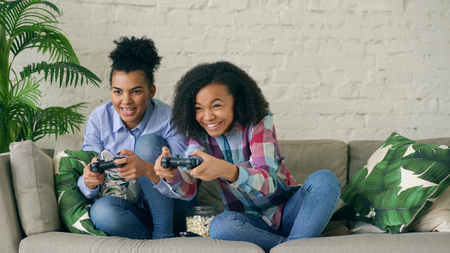 Two mixed race curly girls sitting on couch play console computer games with gamepad and have fun at home