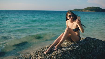 Jonge gelukkige vrouw chatten met vrienden via internet met behulp van smartphone in oceaan strand Stockfoto
