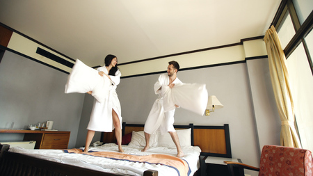Young happy couple in bathrobe fight pillows and have fun on bed in hotel during their honeymoon vacation Stock Photo