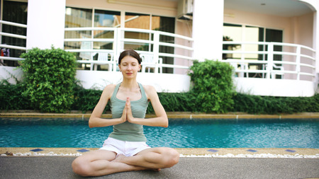 Calm woman doing yoga near swimming pool in hotel on sunny day Stock Photo