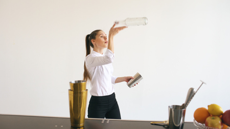 Professinal bartender girl juggling bottles and shaking cocktail at mobile bar table on white background Stock Photo