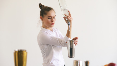 Professinal bartender girl juggling bottles and shaking cocktail at mobile bar table on white background Imagens