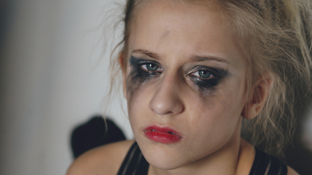 Closeup of young teenage girl dancer crying after loss perfomance sits on floor in hall indoors Stock Photo - 92361786