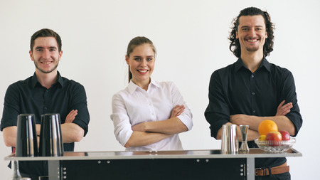 Professinal bartender man and woman smiling at mobile bar table on white background studio