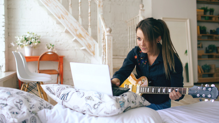 Attractive young girl learning to play electric guitar with notebook sit on bed in bedroom at home Banco de Imagens