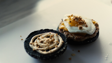 Closeup of grilled black burgerwith sauce and eggs on kitchen board