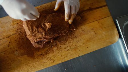 De close-up van de professionele chef-kokmens bereidt vlees met kruid op scherpe raad bij restaurantkeuken voor Stockfoto
