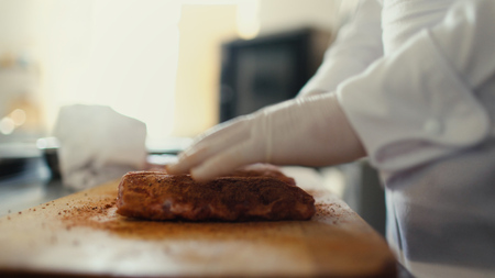 Closeup of professional chef man prepare meat ribs with spice on cutting board at restaurant kitchen