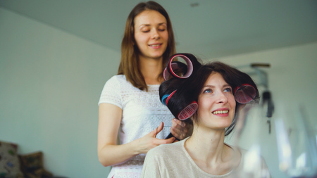 Two happy women friends make fun curler hairstyle each other and have fun at home Imagens