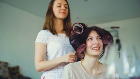 Two happy women friends make fun curler hairstyle each other and have fun at home 版權商用圖片