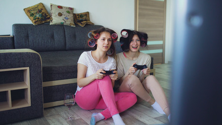Two funny women play console games with gamepad and have fun at home Stock Photo
