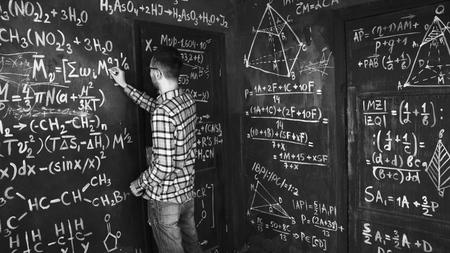 Jonge wetenschapper man schrijft chock in chemische en wiskundige vergelijkingen muur kamer interieur