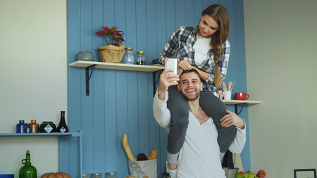 Happy young couple having fun in kitchen at home. Girl is sitting on boyfriends neck while he taking selfie portrait on smartphone camera