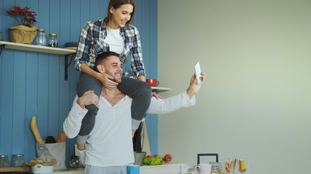 Happy young couple having fun and talking online video call in the kitchen at home. Girl is sitting on boyfriends neck while he holding smartphone