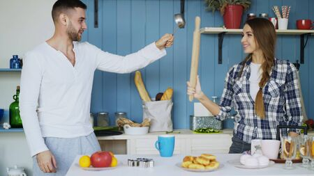 Happy couple having fun in the kitchen fencing with ladle and rolling-pin while cooking breakfast at home Stock Photo