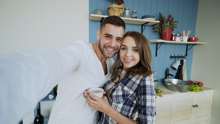 POV of Young happy couple taking selfie photos while having breakfast time in the kitchen at home Stock Photo