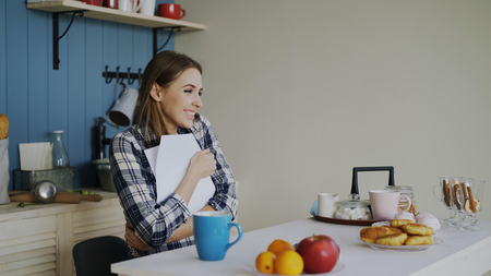 Young happy woman surprised to recieve good news reading letter in the kitchen while have breakfast at home early morning