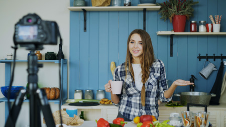 Young attractive woman recording video food blog about cooking on dslr camera in kitchen Stock Photo