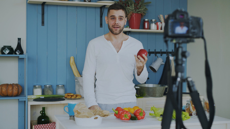 Handsome cheerful man recording video blog about vegetarian healthy food on dslr camera in kitchen at home