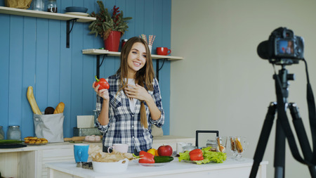 Cheerful attractive woman recording video blog about vegetarian healthy food on dslr camera in kitchen at home Stock Photo