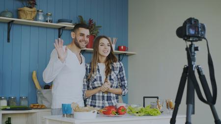 陽気な魅力的なカップルは、自宅の台所でdslrカメラで調理についてのビデオ食品ブログを記録