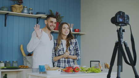 Cheerful attractive couple recording video food blog about cooking on dslr camera in the kitchen at home Stok Fotoğraf