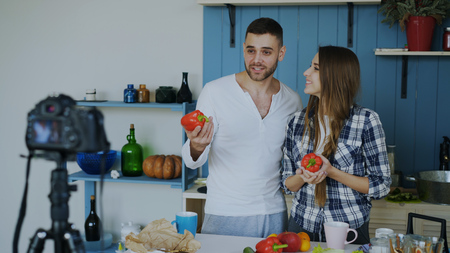 Cheerful attractive couple recording video food blog about cooking on dslr camera in the kitchen at home Stock Photo