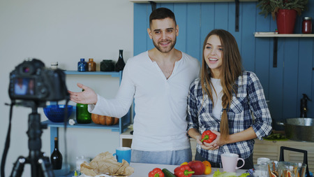 Cheerful attractive couple recording video blog about vegetarian healthy food on dslr camera in the kitchen at home Stock Photo