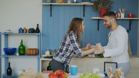 Cheerful and attractive young couple in love dancing together latin dance in the kitchen at home on holidays Stock Photo