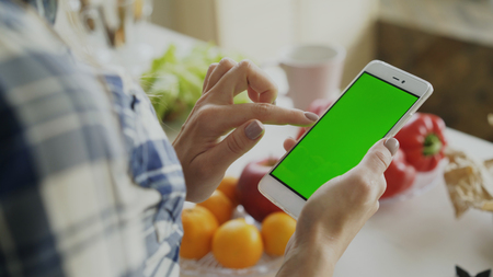 Closeup of womans hand browsing smartphone with green screen on kitchen at home