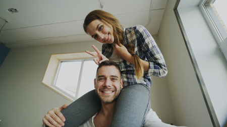 POV of happy smiling and beautiful couple take selfie portrait on smartphone camera while girl sitting on mans neck at home