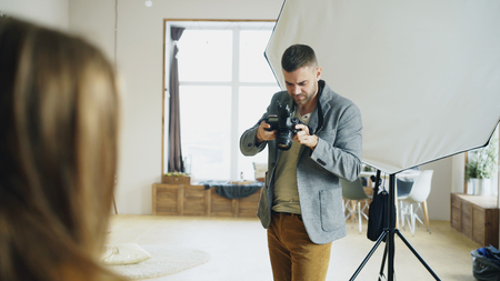 Professional photographer taking photos of model on digital camera working in photo studio Stock Photo