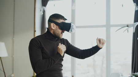 Excited young man with virtual reality headset dancing and play 360 video game at home Stock Photo