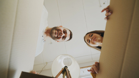 Young happy couple opening cardboard box and looking inside and closing it checking after relocation in new house Stock Photo