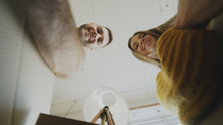 POV of happy couple kissing while opening cardboard box after relocation and looking inside and taking things in new house Stock Photo