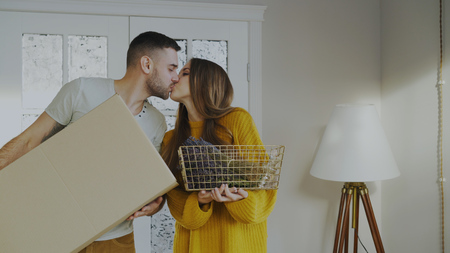 Happy couple happy to enter their new home at first time. Young man kissing his girlfriend Stock Photo