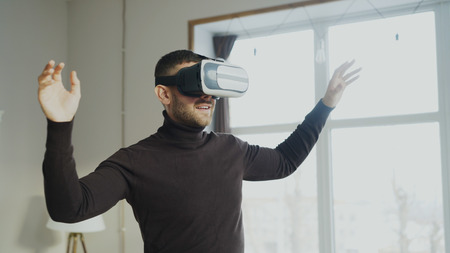 Excited man with virtual reality headset playing 360 video game at home