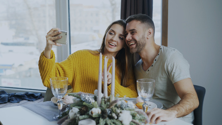 Happy smiling couple having lunch and taking selfie portrait with smartphone at cafe indoors Stock Photo