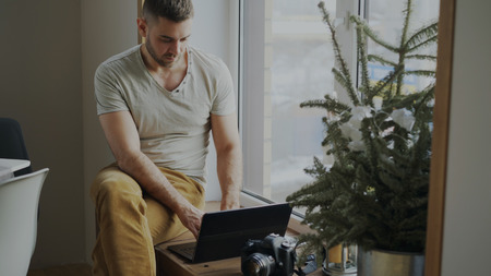 Concentrated male photographer with camera and laptop computer sitting on windowsill at home and sharing her photos to social media
