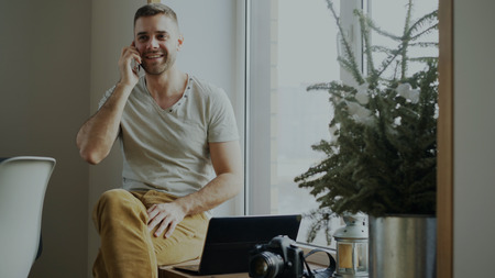 Attractive young man talking phone sitting on windowsill with laptop and camera at home Stock Photo